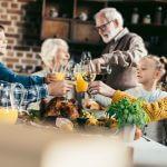 beautiful family clinking glasses on holiday dinner- taxi landskrona trafiken önskar er trygga och säkra lov