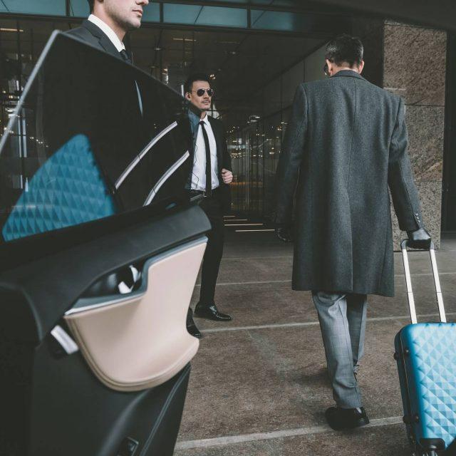 businessman going with blue bag on wheels to airport affärsman med blå resväska till flygplats taxi620