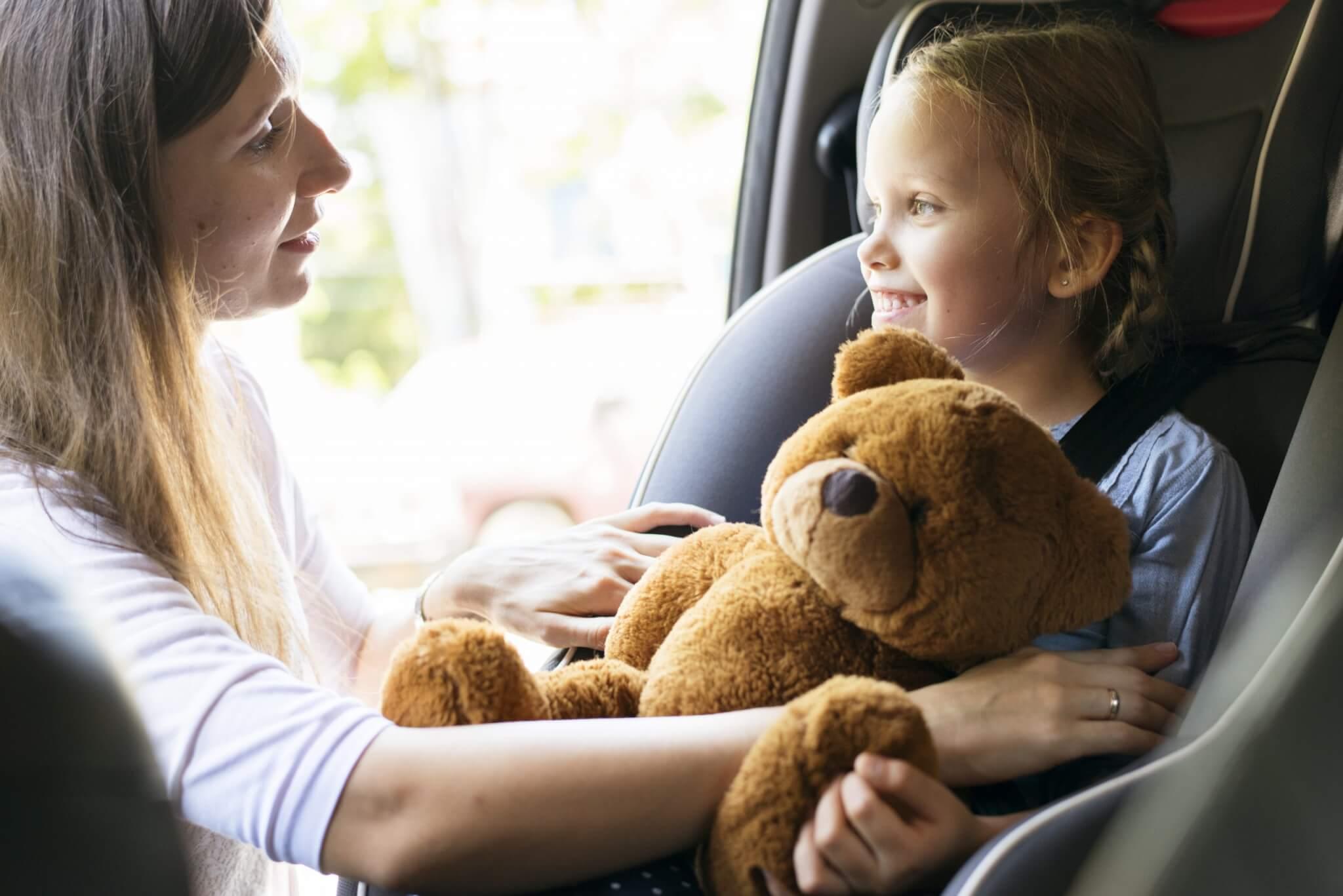 Barnens säkerhet bälteskudde bilbarnstol - Mother helping to put on the seat belt