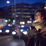 Woman On City Street At Night Ordering Taxi Using Mobile Phone App- taxisäkerhet och hög kvalitet blogg post